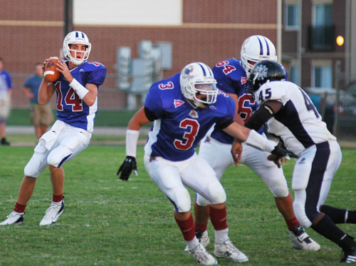 Eric Lucero and Jonathan Wyatt give quarterback Kevin Lauchland time to launch a pass.