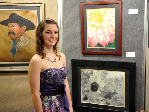 OPSU student, Rachel Helms, shows off some of the fine art work sold at the 14th Annual Paul Farrell Memorial Art Auction held March 7 in Guymon, Okla. —Photo by Sarah Henderson