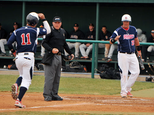 After scoring a run, Nick Crosswhite waits at the plate to congratulate homerun hitter Alfonso Gonzalez.—Kassi Cannon photo