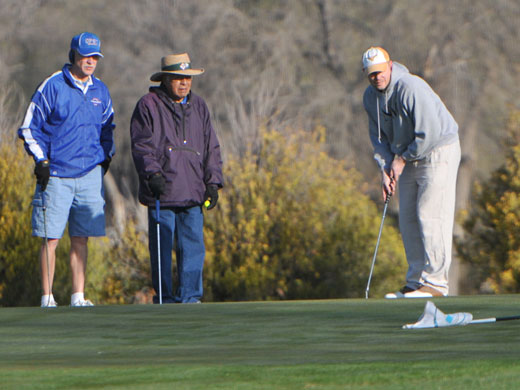 Wayne Manning, left, and Serafin Ramon watch teammate Joe Breeden putt during the Belly Open golf tournament held April 13.—Sage Fischer photo