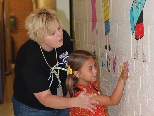 SOEA member Connie Butler helps Braxton, daughter of Brent and Linda Shoulders, leave her handprint on the wall in her school as part of the mural that was painted in Goodwell.—Courtesy photo