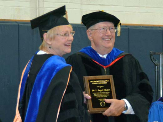 Dr. Dave Bryant presents Dr. Loyet Shafer (left) with a plaque in recognition of her 16 years of service at OPSU during the OPSU Commencement Cermony held May 17.  — Photo by Danae Moore