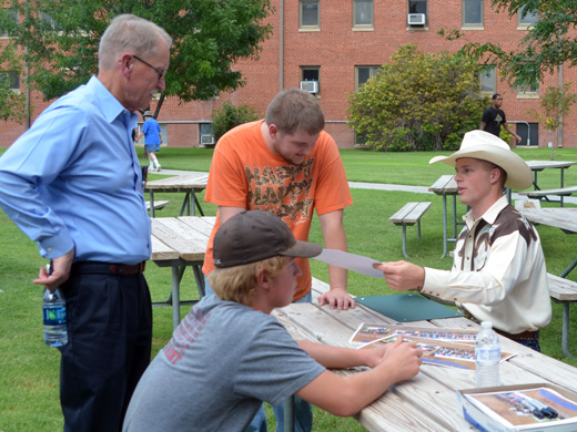 Vice President of Academic Affairs, Dr. Wayne Manning (left) gets an autograph from 2014 College National Champion Bull Rider, Joe Frost (right) at a cook-out on Aug. 21 celebrating the Panhandle State Rodeo Team's success throughout the 2014 season. — Photo by Danae Moore