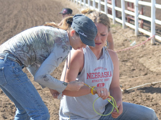 Chancy Harrington, left, examines Callie Schafer's goat tying string. Schafer, a member of the OPSU Rodeo team, is a junior biology major from Yoder, Wyo.—Kelly Darnell photo