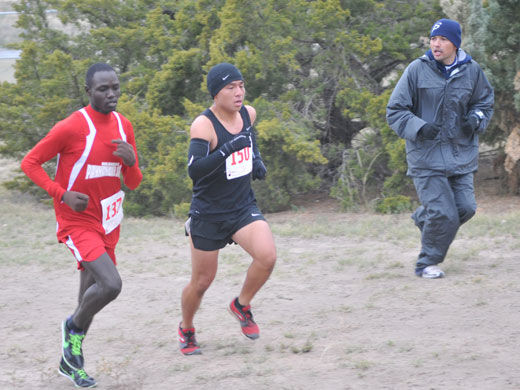 OPSU head cross country coach Victor Esparza cheers on Gideon Busienei (in red) during Saturday's meet.—Justine Gaskamp photo