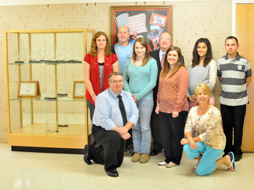 OPSU SOEA Chapter gathers for a picture by their new trophy case. Pictured from left to right: Katlin Vaughan, Jerry Mihelic, Clayton Reed, Caitlyn Christie, Dr. Dave Bryant, Katie Kreamer, Chelsea Ghumm and Omar Holguin. Not pictured: Adviser, Jana Peterson. —Photo by Danae Moore