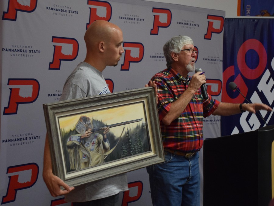 Panhandle State's first Shooting Sports Banquet was September 28 at Hunny's in Guymon. Pictured here Mike Gaitlin (right) auctions off a piece of artwork by Bryon Test. The banquet saw both a live auction as well as a raffle to raise support for scholarships and equipment. —Photo by Danae Moore