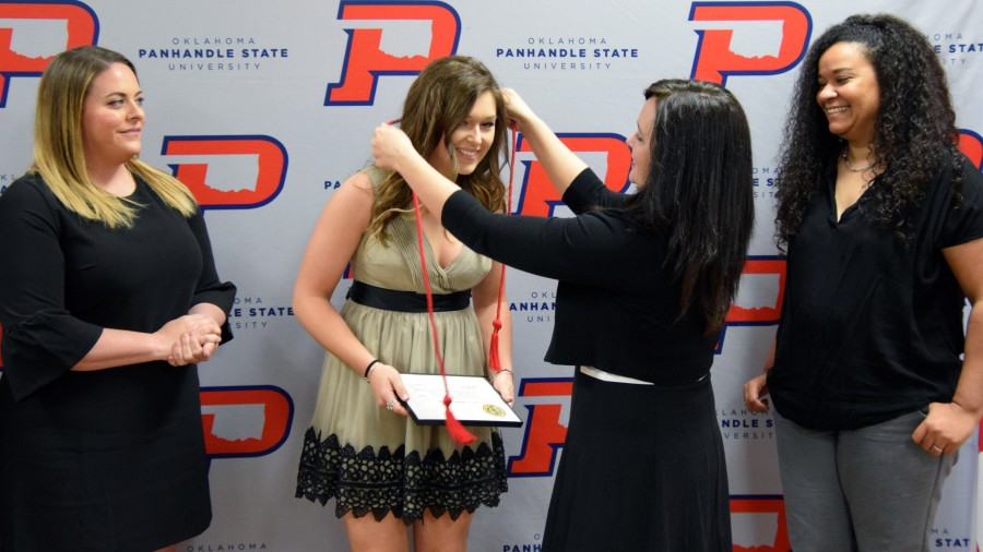 Senior Kayln Moore is presented with a red cord for graduation by Dr. Julie Dinger; also present Meghan Mulcahy, Athletic Director (left) and Head Volleyball Coach Angela Franke (right).-Sydney Dougherty photo<br />&nbsp;