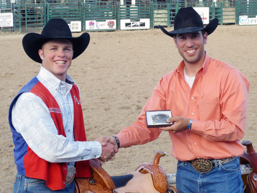 OPSU's Joe Frost, left, earned the Central Plains Region All-Around Cowboy title and accepts the buckle and saddle from Collin Domer, the region's student director.—Sage Fischer